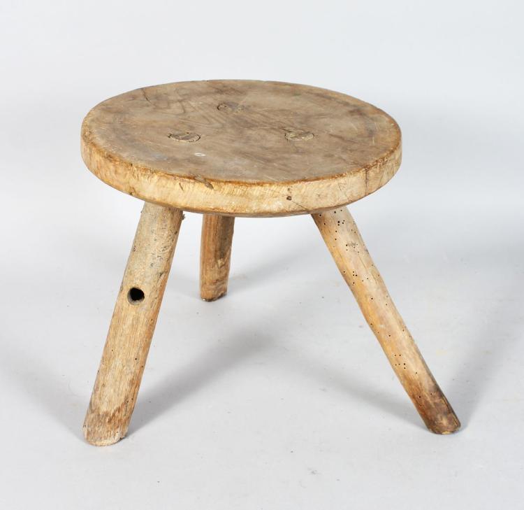 A RUSTIC WOOD CIRCULAR MILKING STOOL, 10ins diameter, on three rustic legs.