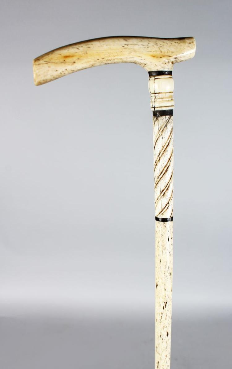 A 19TH CENTURY MARINE IVORY-HANDLED WALKING STICK with turned plain and twisted upper section, on a slender turned shaft.