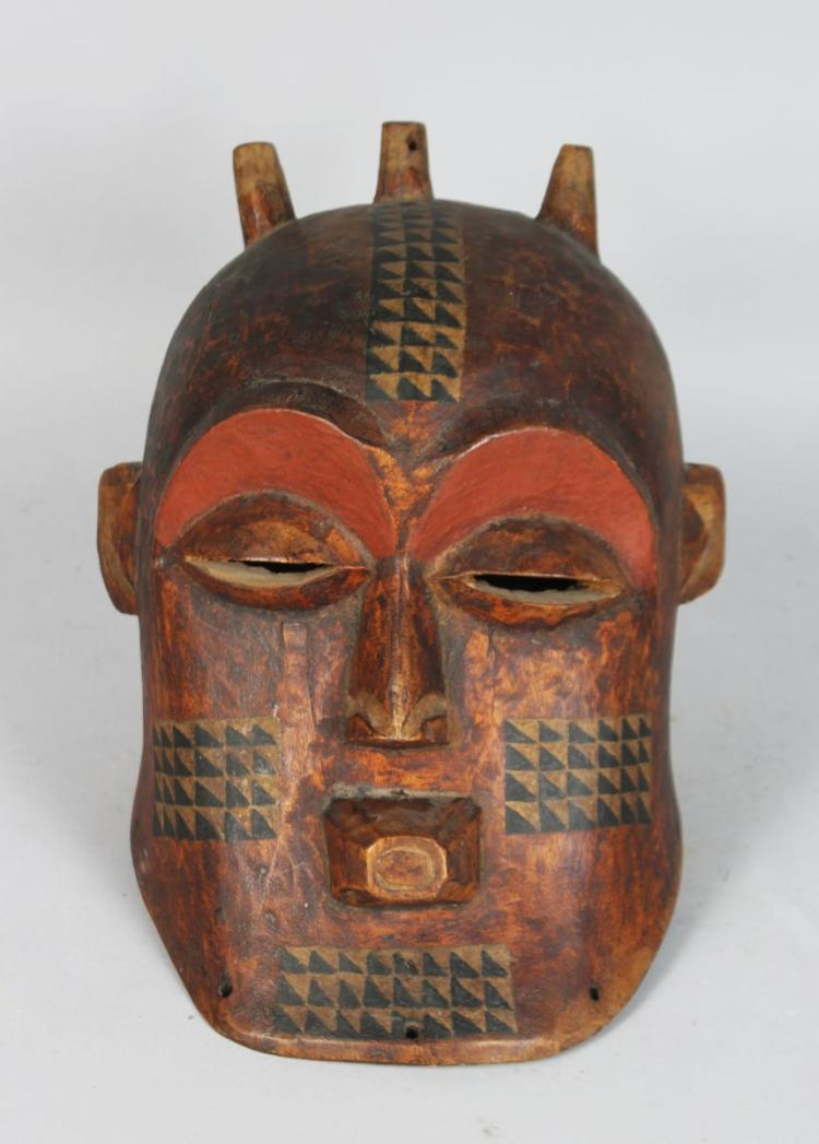 AN AFRICAN CARVED BIOMBO STYLE HELMET MASK with Horns, pierced eyes and mouth with three horns, dark painted patina with painted geometric pattern. 11 inches high.