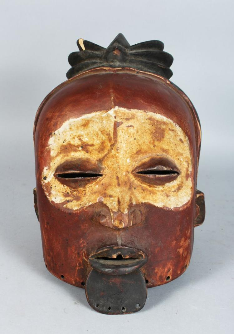 AN ASIAN POLYCHROME CARVED WOODEN HELMET MASK, finely carved and painted 12 inches in height.