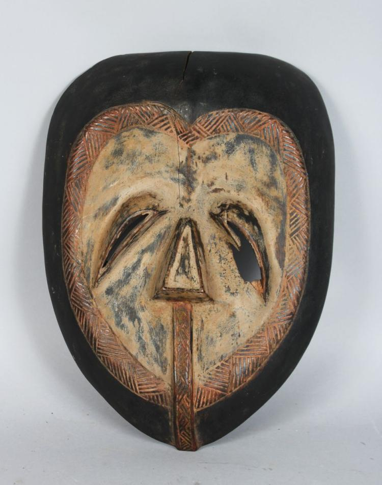 AN AFRICAN CARVED WOOD MASK, TSOGO STYLE, pierced eyes, with carved incised pattern, with a dark patina with painted central section. 12 inches high.