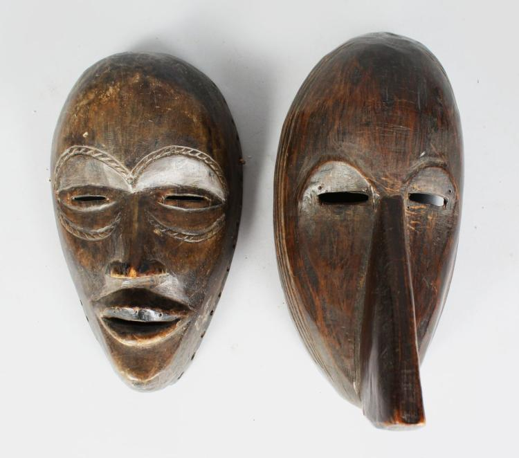 TWO AFRICAN CARVED WOOD MASKS, with pierced eyes, with carved incised patterns, each with a dark patina. Largest 12 inches high (2).