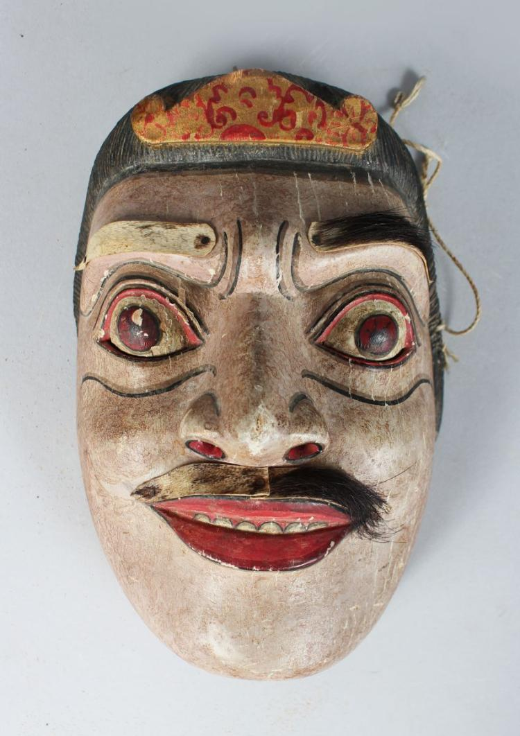 A POLYCHROME CARVED WOODEN DANCE MASK (TOPENG) dramatically modelled with bulging eyes, moustache and eyebrows, finely carved and painted 8 x 5 inches.