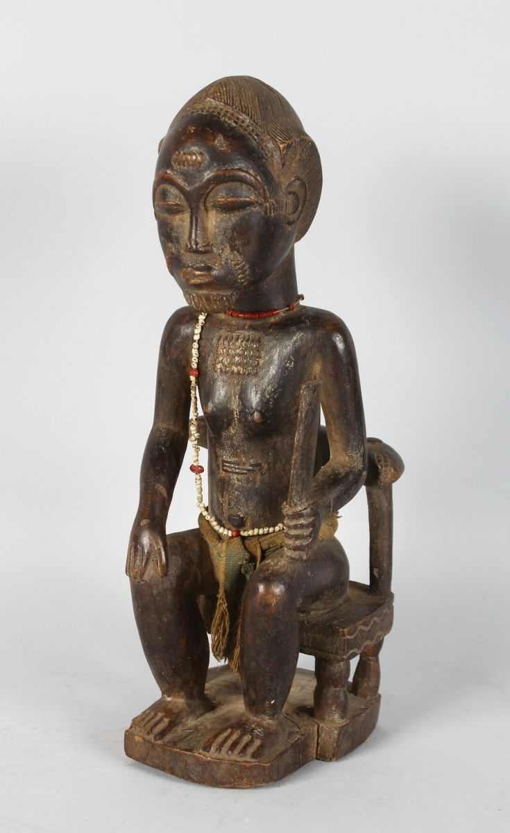A GOOD CARVED WOOD TRIBAL SEATED MAN holding a knife. 15ins high.