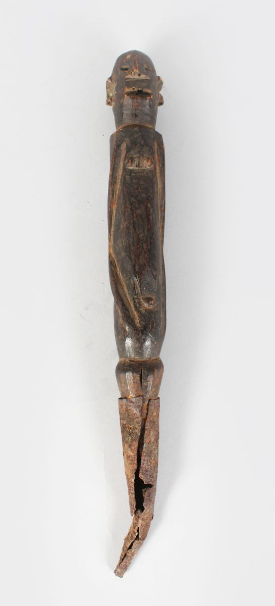 AN OLD CARVED WOOD AND METAL TRIBAL HOUSE SPIKE, head and body of a man. 14ins long.