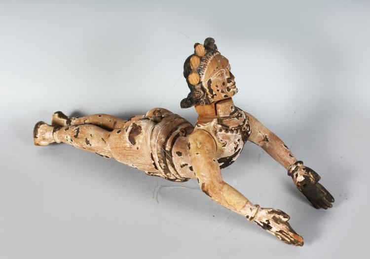 A RARE INDIAN CARVED WOOD DEITY. 19ins long.