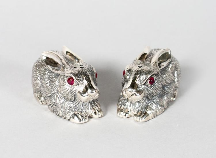 A GOOD PAIR OF SILVER RABBIT SALT AND PEPPERS with ruby eyes.