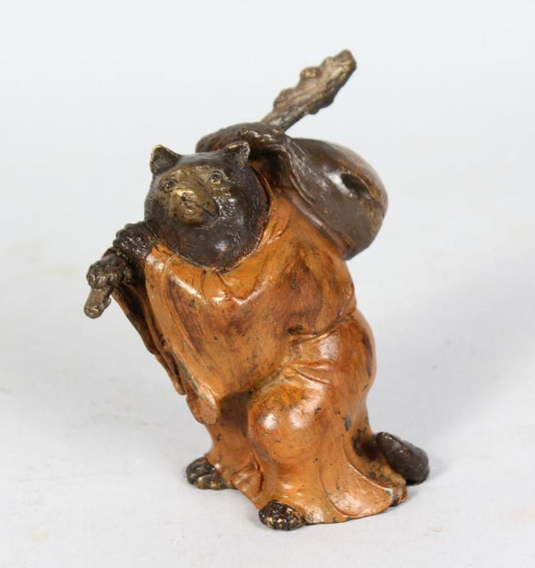 A SMALL COLD PAINTED BRONZE OF A BEAR, carrying a stick and bag on his shoulder. 4ins high.