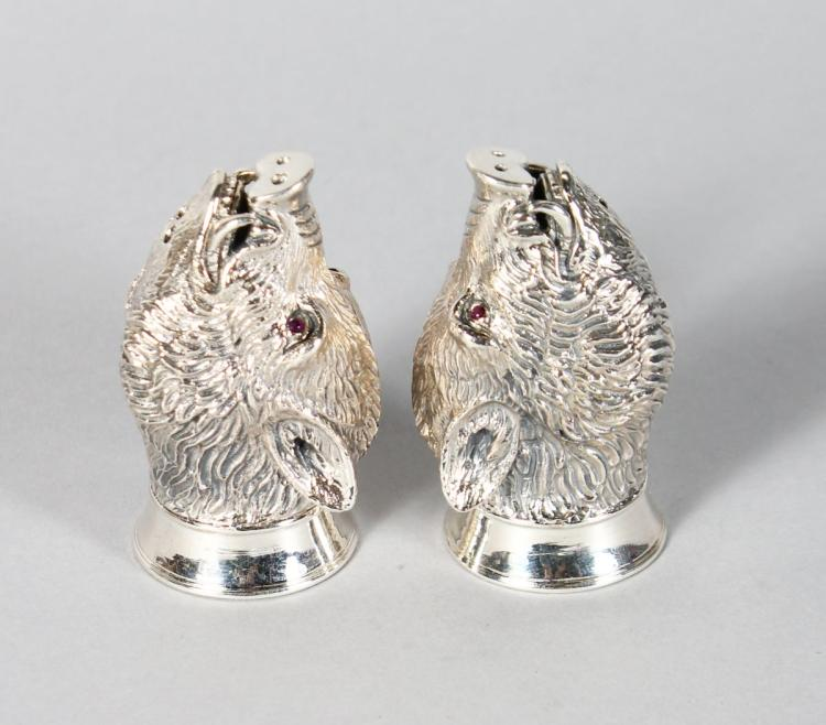 A GOOD PAIR OF SILVER BOAR'S HEAD SALT AND PEPPERS with ruby eyes.