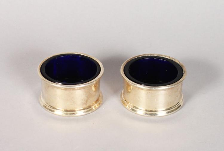 A PAIR OF CIRCULAR SILVER SALTS with sapphire blue liners, LONDON.