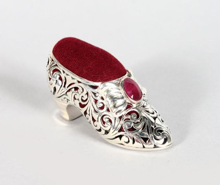 A PIERCED SILVER AND RUBY SET SHOE PIN CUSHION.