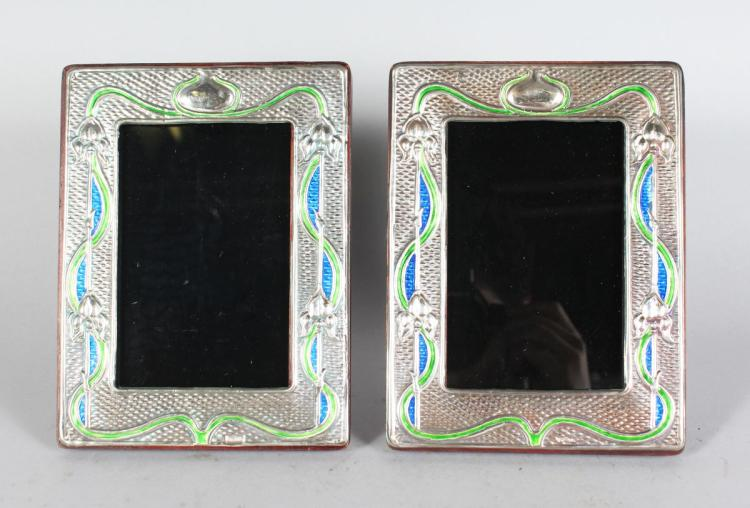 A PAIR OF SILVER AND ENAMEL PHOTOGRAPH FRAMES. 7ins high x 6ins wide.