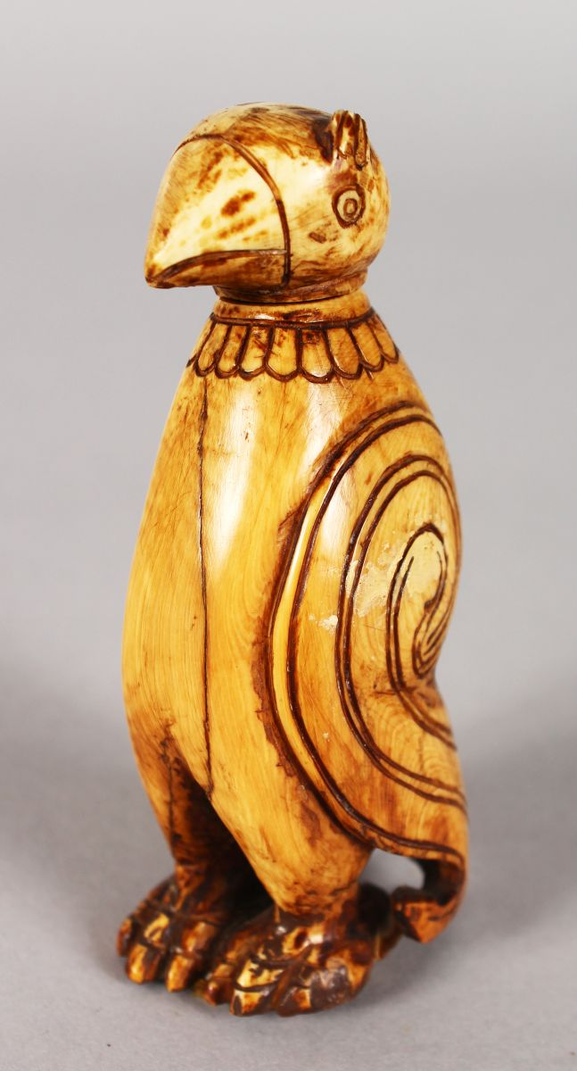 AN EARLY INUIT CARVING OF A PENGUIN, standing upright, the detachable head forms a stopper. 9cms high.