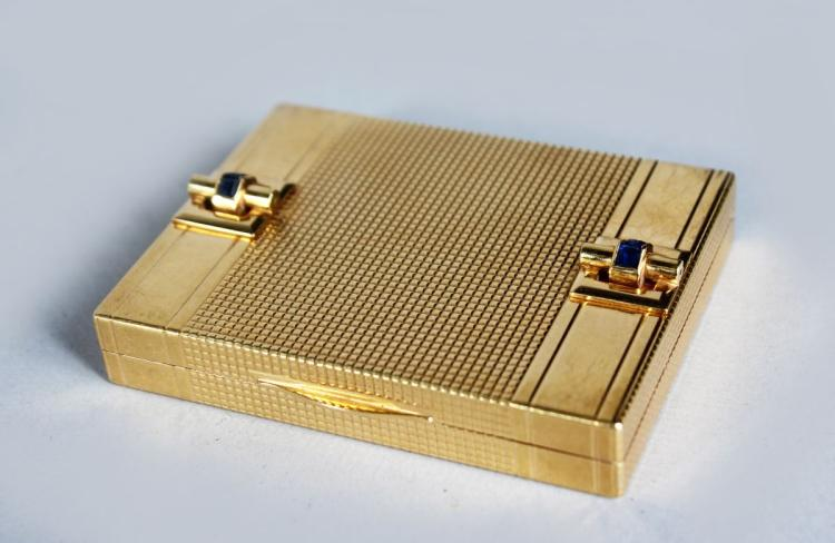 A GOOD ART DECO DESIGN GOLD COMPACT, with engine turned decoration, set with four sapphires. stamped 14K, 6361. 2.5ins wide.