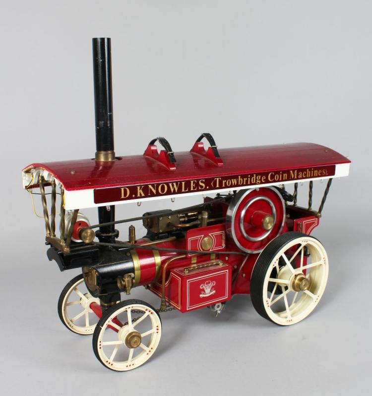 A 'Markie' model of a fairground showman's traction engine 'Trowbridge Coin Machines', built by Tony Pearce in 1983. The boiler being spirit fired with open crank and single cylinder having fitted pressure gauge, regulator, disc flywheel, worm and chain steering, generator, brake to back wheel having fitted road tyres. The canopy with extension chimney mounted on brass olives. Finished in red and white livery. Boiler: appears never fired. with original receipt. Measurements: Canopy 52cm x 20cm. Total height 30cm.