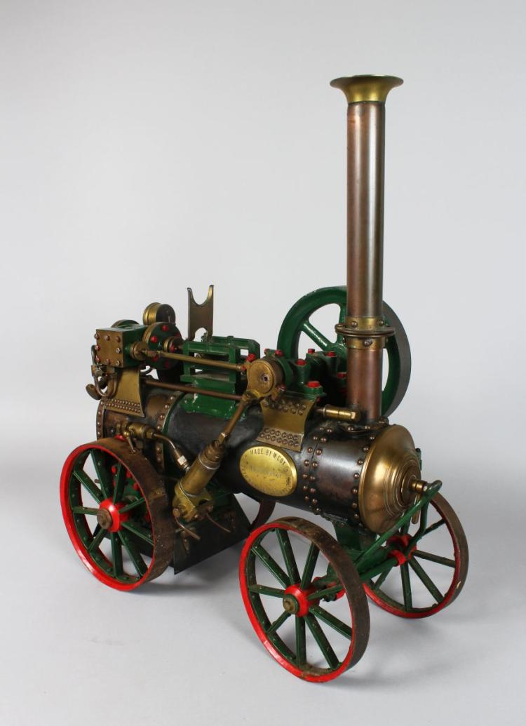 A Superb Live Steam Scale Model of a portable traction Engine or Steam Tractor, built by W Cox, North Bradley, Trowbridge. In green with brass brightwork, red spoked wheels, solid flywheel and burner, extension chimney, length 52 cm 56 high No boiler history available.