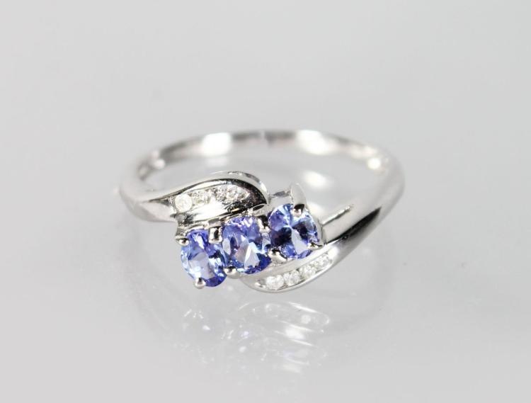 A 9CT WHITE GOLD, TANZANITE AND DIAMOND RING.