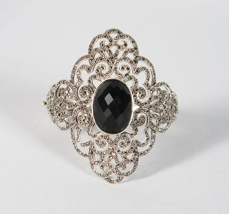 A LARGE VICTORIAN STYLE ONYX AND MARCASITE BANGLE.