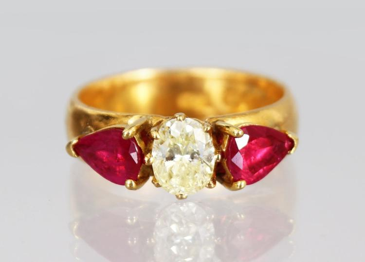 A 22CT YELLOW GOLD RUBY AND DIAMOND RING, the central diamond flanked by two pear shaped rubies.