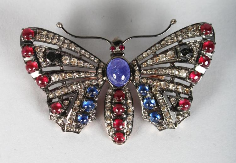 A LARGE BUTTERFLY BROOCH, set with cabochon rubies and sapphires. 3ins wide.