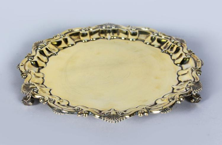 A SILVER GILT PIE CRUST SALVER with shell border on three knurled feet. 10.5ins diameter. Birmingham 1901. Maker: BB. Weight 18ozs.