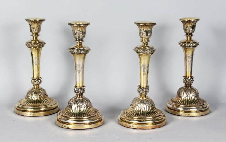 A VERY GOOD SET OF FOUR SILVER GILT CANDLESTICKS on circular bases, with cast acanthus leaves. 12ins high. Bears Crest