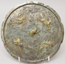 A CHINESE TANG STYLE GILDED & SILVERED BRONZE MIRROR, decorated in relief w