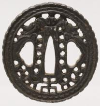 A JAPANESE MEIJI PERIOD IRON TSUBA, pierced with a design of confronting dr