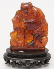 A 19TH CENTURY CHINESE AMBER CARVING OF AN IMMORTAL, together with a fixed