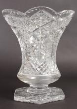 A HEAVY CUT GLASS THISTLE SHAPED FLOWER VASE on an octagonal base. <br>11ins high.