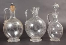 THREE ENGRAVED WINE JUGS AND STOPPERS.