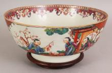AN 18TH CENTURY CHINESE QIANLONG PERIOD FAMILLE ROSE MANDARIN PORCELAIN BOWL, together with a wood stand, the sides painted in vivid enamels with two figural panels, the bowl 8.9in diameter & 3.8in high.