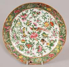 A 19TH CENTURY CHINESE CANTON FAMILLE ROSE PORCELAIN SAUCER DISH, painted with an exotic bird, butterflies, fruit and floral sprays, 9.5in diameter.