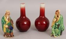 A SMALL PAIR OF 20TH CENTURY CHINESE SANG-DE-BOEUF PORCELAIN BOTTLE VASES, each base with a seal mark, 5in high; together with two glazed pottery figures of sages, 4.6in high. (4)