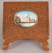A 19TH CENTURY INDIAN MINIATURE PAINTING ON IVORY OF THE TAJ MAHAL, mounted in a carved sandalwood display frame, the frame 3.8in wide & 4.2in high.
