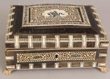 A 19TH/20TH CENTURY INDIAN VIZAGAPATUM STYLE IVORY & HORN RECTANGULAR BOX, with hinged cover and lined with sandalwood, the horn exterior onlaid with black engraved ivory panels and borders, the box supported on claw feet, 8.7in x 6.9in x 3.75in high.