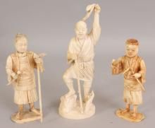 A SIGNED JAPANESE MEIJI PERIOD IVORY OKIMONO OF A FISHERMAN, holding a pole, a crab on a stump beneath him, the base with an engraved signature, 8.75in high; together with two smaller sectional bone ivory okimono of standing farmers, 6.75in & 6.3in high. (3)
