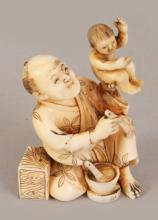 AN UNUSUAL SMALL SIGNED JAPANESE MEIJI PERIOD IVORY OKIMONO OF A KNEELING MAN, holding a brush in one hand and bearing aloft an infant with the other, the base with an engraved signature, 2.3in high.