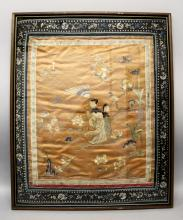 A 19TH CENTURY FRAMED CHINESE ORANGE GROUND SILK EMBROIDERY, decorated in satin stitch and gilt thread with a lady and attendant in a garden setting, the frame 27.5in x 22.5in.