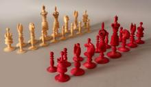 A GOOD QUALITY 19TH CENTURY INDIAN SECTIONAL IVORY CHESS SET, one side natural, the other side stained red, the King & Queen pieces with pierced crowns, together with a hardwood box, the sliding cover with an onset ivory catch, the box 10.1in x 5.6in x 4.2in high, the Kings 4.6in high, the pawns 1.8in high.