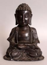 A GOOD 16TH CENTURY CHINESE MING DYNASTY BRONZE FIGURE OF BUDDHA, seated in dhyanasana, the hems of his robes with floral engraving, his chest engraved with a swastika, 5.25in wide at widest point on base & 6.9in high.