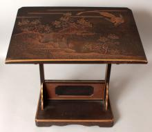 AN UNUSUAL FINE QUALITY JAPANESE MEIJI PERIOD LACQUERED WOOD LECTERN, the sloping surface decorated with a ho-ho phoenix in flight above a rockwork and foliage bordered stream, the lectern with engraved silver-metal supports, 19.2in wide x 11.3in deep x 17.25in high.