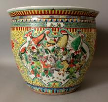 A GOOD LARGE EARLY 20TH CENTURY CHINESE FAMILLE VERTE PORCELAIN FISHBOWL, the sides painted with shaped panels of officials and of warriors reserved on a yellow ground embellished with scrolling foliage, the interior with carp, the base unglazed, 14.5in wide at widest point & 12.75in high.