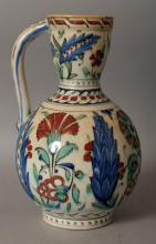 A 19TH/20TH CENTURY ISLAMIC ISNIK EWER, painted with stylised foliate motifs, 6.5in wide at widest point & 10.5in high.