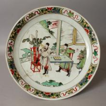 A CHINESE KANGXI PERIOD FAMILLE VERTE PORCELAIN SAUCER DISH, circa 1700, the interior painted with a scene of two animated men observing from a terrace, the rim with ribboned emblem vignettes reserved on a ground of scattered flowerheads, 10.7in diameter.