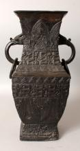 A CHINESE SQUARE SECTION BRONZE VASE, the sides cast with multiple archaic borders, the neck with double dragon-head and loose ring handles, 13.75in high.