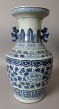 A 19TH CENTURY CHINESE BLUE & WHITE PORCELAIN VASE, the sides painted with bands of leaf and scroll stemmed peony between formal borders, 15in high.