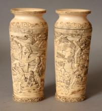 A GOOD PAIR OF EARLY 20TH CENTURY JAPANESE CARVED IVORY VASES, each carved with a continuous figural village scene, 5.6in high.