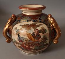 AN EARLY 20TH CENTURY SIGNED JAPANESE MEIJI PERIOD SATSUMA EARTHENWARE THREE HANDLED VASE, each handle of moulded dragon form, the sides painted with a landscape panel and with two panels of deities, 8in wide at widest point & 6.8in high.