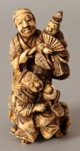 A SIGNED JAPANESE MEIJI PERIOD STAINED IVORY OKIMONO OF A PUPPETEER, in the company of his son and holding aloft a puppet bearing a fan, the base with a signature in red, 3.1in high.